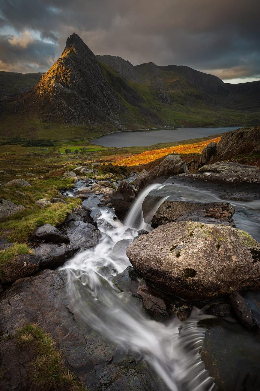 Dawn light shines on Tryfan mountain, viewed from the waterfalls above Llyn Ogwen, Snowdonia