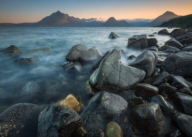 The sun rises of the rocky coast at Elgol, Isle of Skye