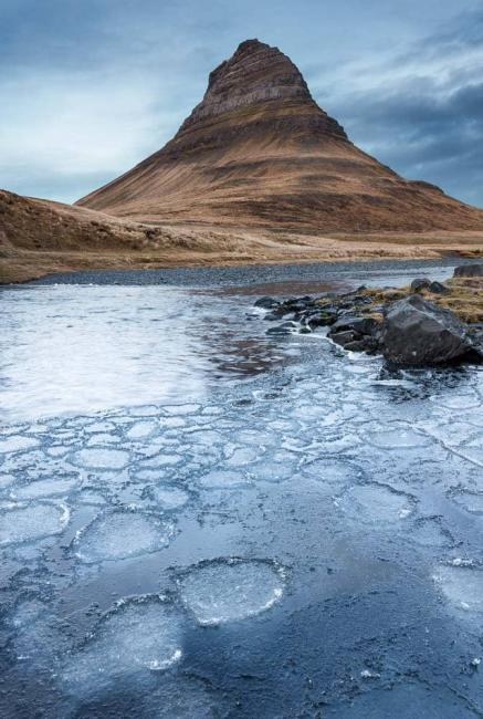 Ice gathers in a poo in front of Kirkjufell Mountain