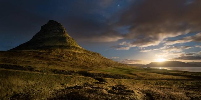 The moon rises over Kirkjufell mountain in Iceland