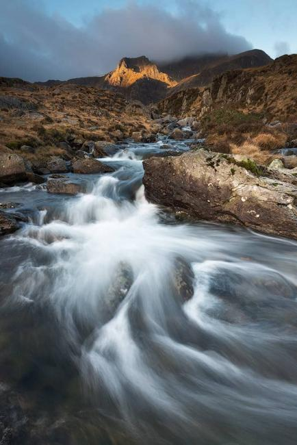 Sun rises over the stream at Llyn Idwal, Snowdonia