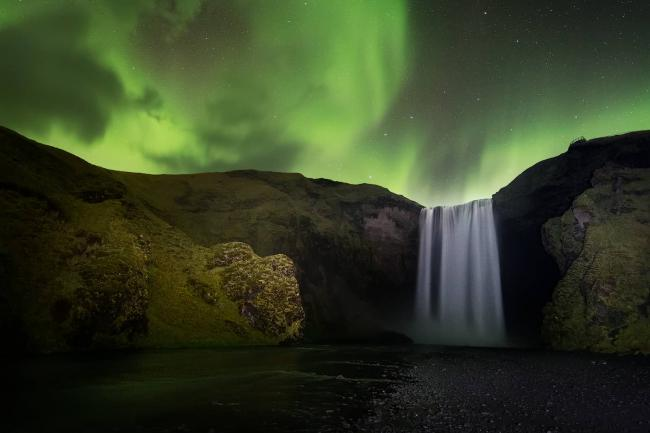 Northern Lights in the night sky over Skógafoss waterfall, Iceland