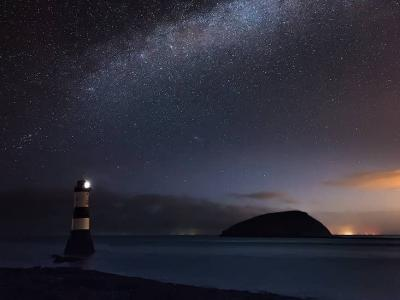 The milky way in the night sky behind Penmon Lighthouse